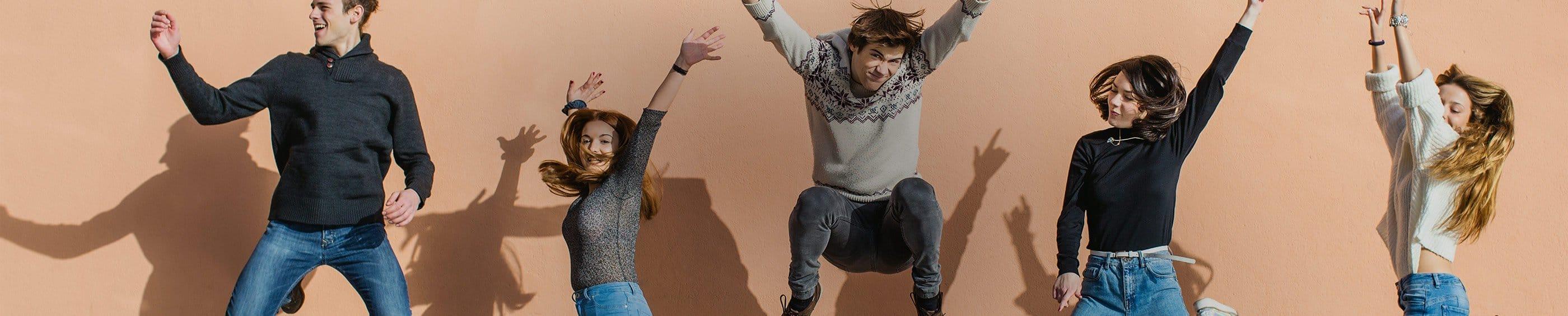 Una foto perfectamente sincronizada de un grupo de amigos saltando en el aire con las manos en el aire