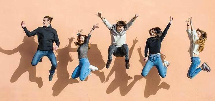 Un grupo de amigos riendo y brincando con sus manos en el aire