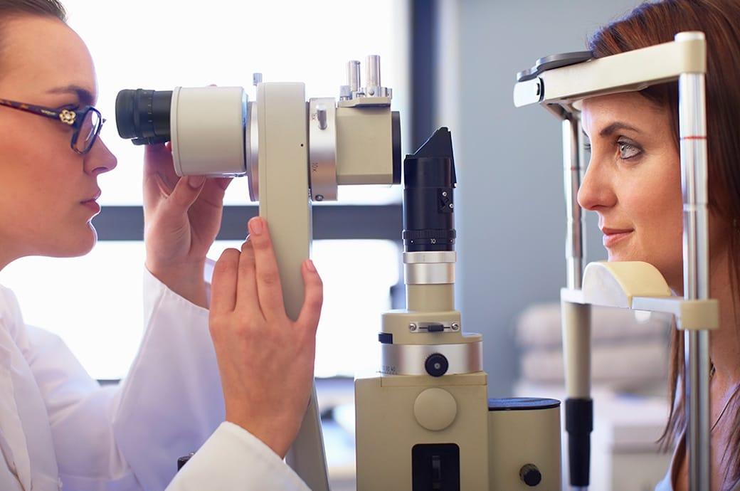 Una vista lateral de un oculista y una mujer joven mirando a través de una cámara de retina