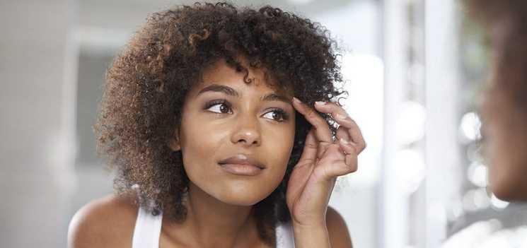 Una mujer joven mirando sus ojos en el espejo